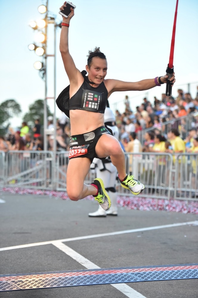 Amelia leaping in the at the finish at runDisney Star Wars Dark Side Half Marathon